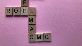 betekenis van lmao uitgebeeld door houten blokjes met de letters LMAO, rofl en omg erop