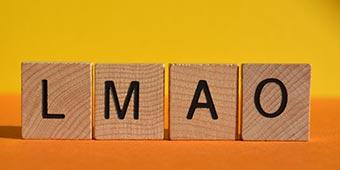 betekenis van lmao uitgebeeld door houten blokken met de letters LMAO erop