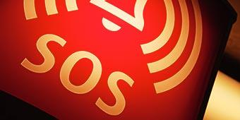 betekenis van sos uitgebeeld door alarm-icoon met de letters SOS eronder op rode achtergrond