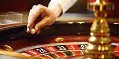 betekenis van roulette uitgebeeld door croupier die balletje in roulettewiel gooit
