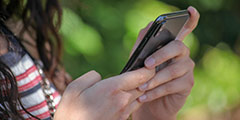 betekenis van sfs uitgebeeld door meisje dat haar smartphone vasthoudt in 2 handen