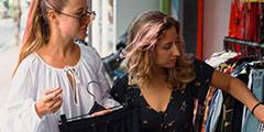 betekenis van afkorting zgan uitgebeeld door twee jonge vrouwen die tweedehands kleding bekijken op de markt