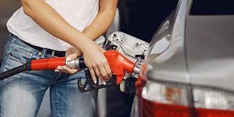 betekenis van fossielvrij uitgebeeld door vrouw die benzine tankt voor auto