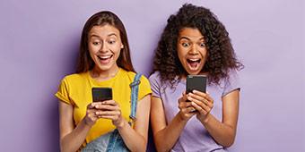betekenis van afkorting hmu uitgebeeld door twee meisjes met smartphones
