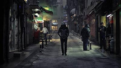 straattaal herres uitgebeeld door jongere die op donkere straat loopt