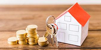 onder bod (hypotheek) uitgebeeld door papieren huisje, huissleutels en muntgeld op houten tafel