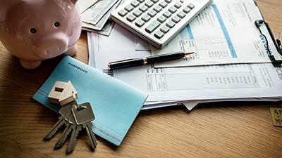onder bod (hypotheek) uitgebeeld door huissleutels, spaarvarken en rekenmachine op bureau