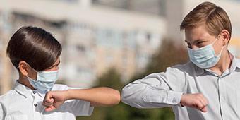 betekenis van pandemie uitgebeeld door twee jongens met mondkapjes die elkaar begroeten met elleboog aanraken