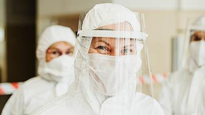 betekenis van pandemie uitgebeeld door ziekenhuismedewerkster met mondkapje en face shield