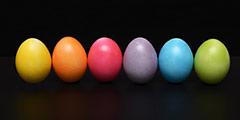 betekenis van pasen uitgebeeld door 6 paaseieren van verschillende kleuren op een rij