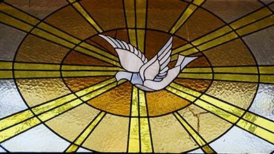 betekenis van pinksteren uitgebeeld door witte duif in glas-in-lood-raam in kerk