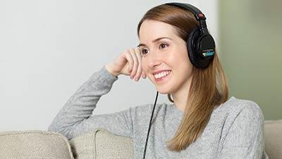 betekenis van podcast uitgebeeld door jonge vrouw zittend met koptelefoon op