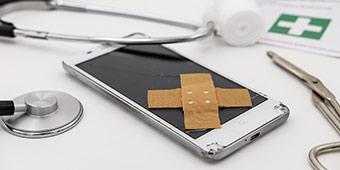 betekenis van refurbished uitgebeeld door smartphone met pleisters erop