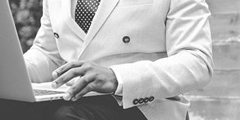 acquisitie betekenis uitgebeeld door man in pak achter laptop