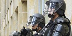 polarisatie betekenis uitgebeeld door politie in beschermde kleding en helm bij rellen