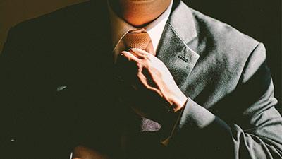 betekenis van pragmatisch uitgebeeld door close up van zakenman die zijn stropdas goed doet