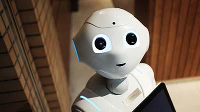 betekenis autonomie uitgebeeld door een witte robot die je aankijkt