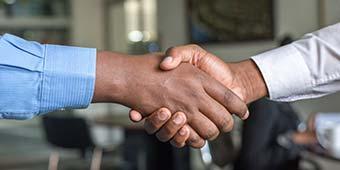 consensus betekenis uitgebeeld door twee mannen die hand schudden