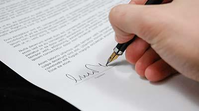 consensus betekenis uitgebeeld door hand die contract tekent