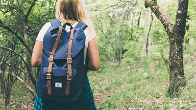 betekenis tassenverslaafd uitgebeeld door vrouw met blauwe rugzak