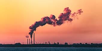 wat is co2 neutraal bouwen uitgebeeld door rokende schoorsteen van fabriek die energie opwekt